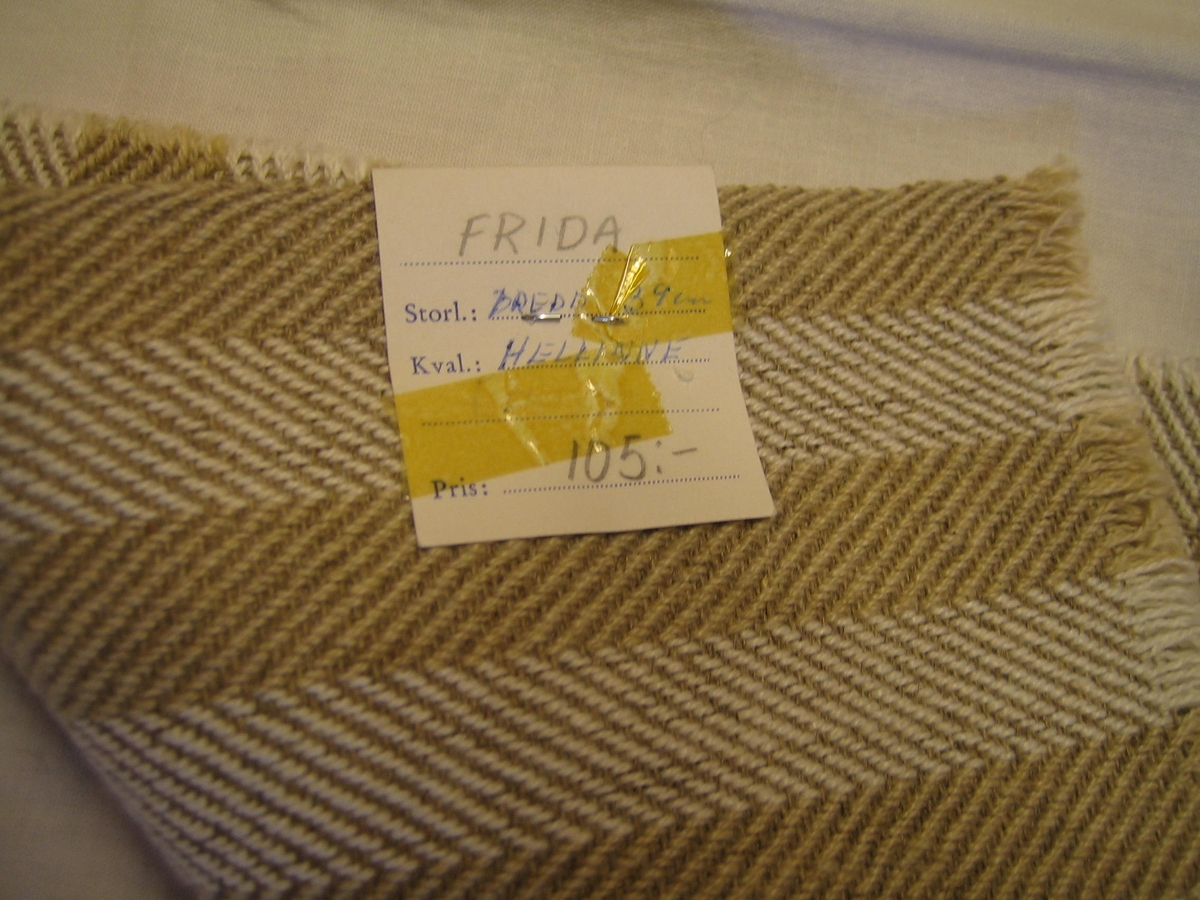 """Vävprov på löparväv Frida i hellinne med oblek och blekt lin i varpen och oblekt lin som inslag. Löparen är vävd i spetskypert 18 mm breda ränder. En lapp är fastsatt med texten: """"FRIDA Storl: BREDD 39 cm, Kval: HELLINNE, Pris: 105:-"""" på ena sidan och texten: """"SKARABORGS LÄNS HEMSLÖJDSFÖRENING SKÖVDE-LIDKÖPING"""" på andra sidan."""