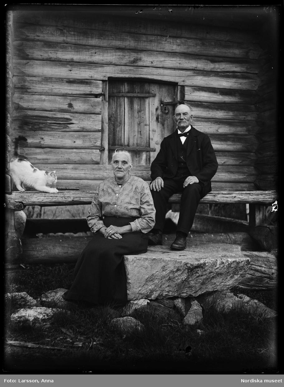 Lantbrevbäraren Erik Stolpe (1854-1956) i Heden med hustrun Klara (1866-1956), sittande framför härbre.