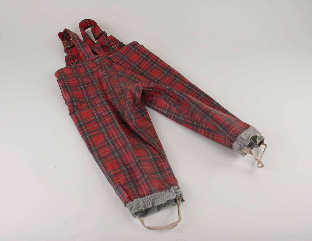 Rutiga galonbyxor med hängslen.  De konfektionssydda byxorna är rutiga i grönt, gult och vitt på röd botten. Två spännen för reglerbara hängslen i metall. Tryckknappar på sidorna, resår vid fötterna samt resårband att sätta under fötterna. Byxorna är välanvända med nött ytskick. Flera sömmar är lagade och axelbanden är förlängda med röd textil. Resåren under fötterna är utbytt.