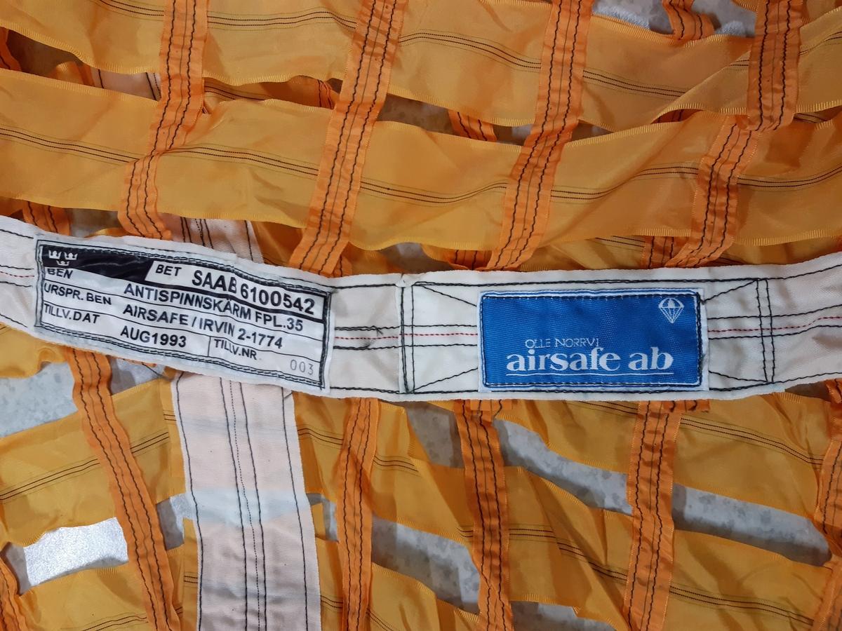 """Antispinnskärm, bestående av orange textil samt vita linor. Medföljer en mindre vit skärm, märkt """"IRVIN 2"""", denna sammanknuten med en brun textil påse. Samt en vit lina med stålvajer och metallfäste. Därtill två tygstycken med ögglor och ett mindre tillhörande textilt fragment."""