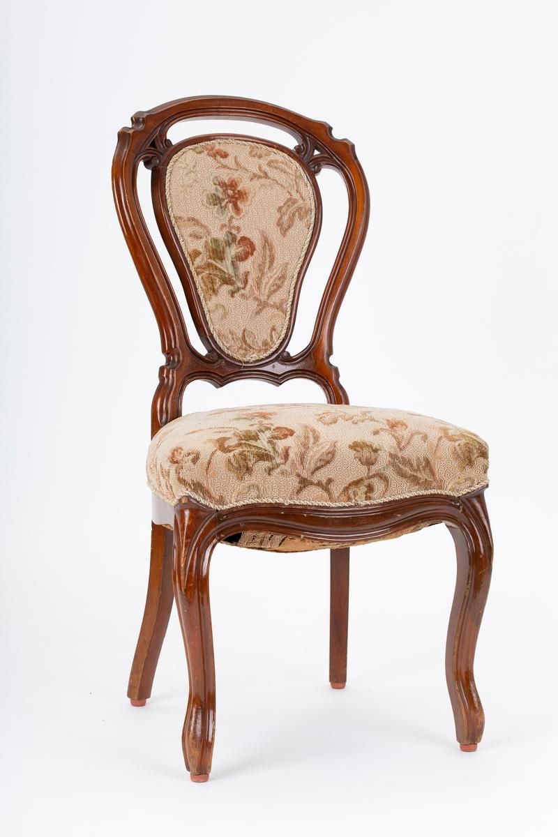 Spisestue/stue stol.  4 stk. Åpen rygg, profilert treramme og stofftrukket ryggpute, Sete med spiralfjærer og stopp. Sarg profilert foran. Buet forben med profil.  Sekundært møbeltrekk i  blomstret ullbouclet. Nyrokokko. Giver kjøpte og møblene til eget bruk på månedsauksjon i Drøbak. De var tidligere brukt i frøknene Holstads Pensjonat i Drøbak Stolene ble brukt sammen med FHM.05256.A og FHM.5236.1.2 - tilhører samme møblement