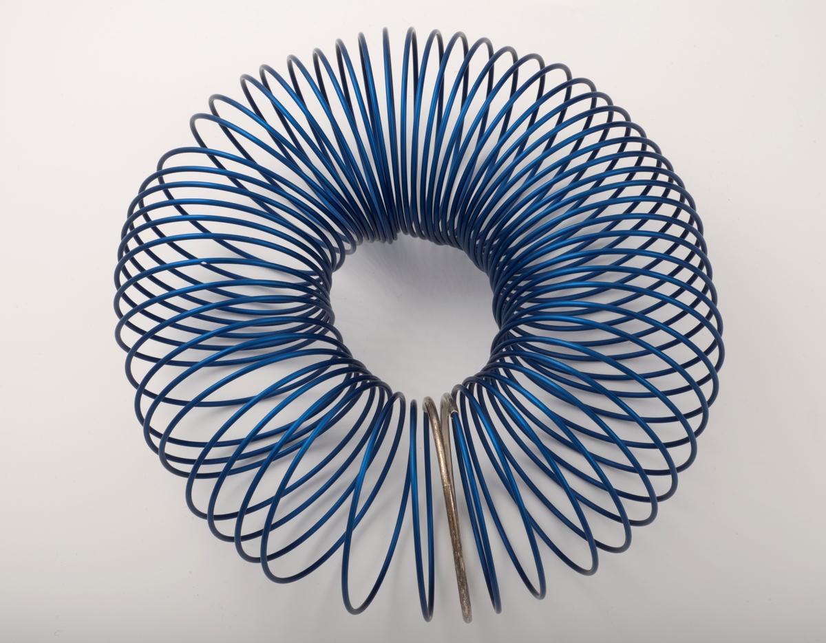 Halssmykke satt sammen av en spiral av eloksert aluminium (blå). Ett ledd i spiralen er uført i sølv. Smykket er mykt og føyer seg etter hals og skuldre, men beholder samtidig sin form.