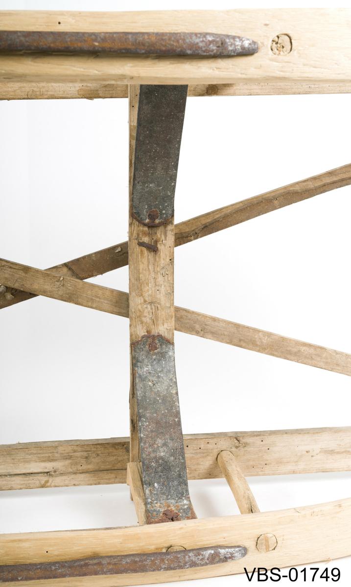 Liten og enkel kjelke med to tverrstenger i form av et kors på toppen. To tynne jernskoning  på bunnen. På innsiden har den to jernforsterkninger (foran) og to andre treforsterkninger (bak).