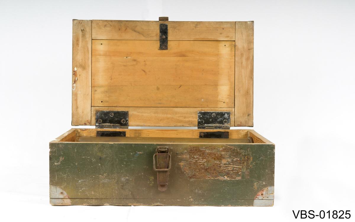 Mørkegrønn trekasse med lokk med klemme-hengsler til å stenge kassen. Det er også jernbeslag på hvert av hjørnene på kassen, lokket og rommet. Det er festet jernhåndtak på hver av kortsidene til kassen. Kassen inneholder en tomhylse til granat i messing: 10 cm fra kanon modell nr. 17.