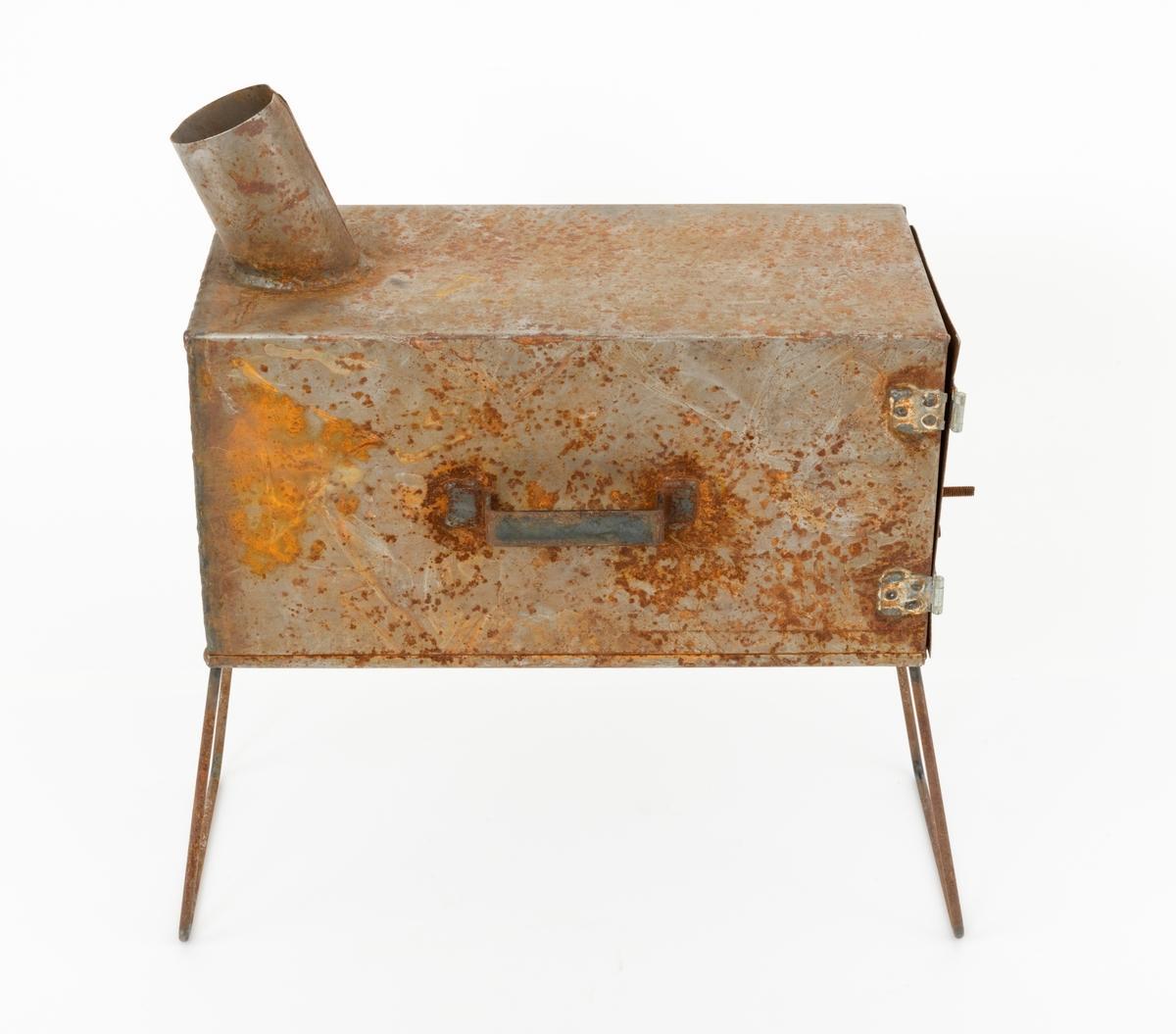 Rektangulær ovn, lagd for bruk i små hviletelt som ble markedsført for skogbruket, der det ble arbeidet i all slags vær og ofte på steder der det ikke var noe husrom å gå inn i når en skulle kvile og spise medbragt matpakke. Ovnen er lagd som en rektangulær beholder - 48,5 centimeter langt, 24 centimeter bred og 24 centimter høy - av falset jernblikk. I den ene tverreden er det påhengslet ei dør, som også er lagd av jernblikk. Den er festet ved hjekp av to gangjern, som dels er naglet, dels punktsveiset til blikket. På forsida av dørbladet er det ei sirkelrund trekkregulerende luke (diameter 7,7 centimeter). Den er lagd av støpejern og festet til en gjenget sentralakse. Ved dørbladets ytterkant er det pånaglet et bandjern, som kunne smøyes inn bak et bandjern som var sveiset fast til «dørkarmen» når brennkammeret skulle stenges. På undersida av ovnen, ved ytterendene, er det festet utfellbare rammer (22.5 X 24 centimeter), lagd av 8 millimeters rundjern. Disse skulle fungere som bein under ovnen. På ei av sideflatene er det påsveiset et handtak, lagd av tommebredt bandjern, som ovnen skulle løftes i når den ble flyttet fra et brukssted til et annet. Bakerst på oversida av ovnen stikker det ut et noe bakoverskrånende cirka 11,5 centimeter langt blikkrør med diameter på snaut 8 centimeter. på dette skulle det antakelig tres en forlengelse, et avløpsrør som førte ovensrøyken ut av teltet.