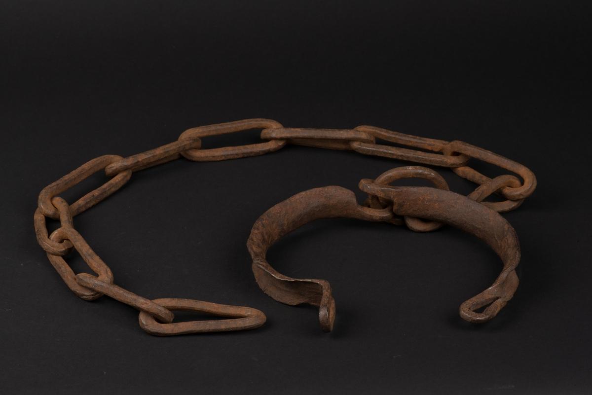 Halsjärn med kedja av järn. Halsringen är i två delar och sitter ihop med en ring där kedjan sitter, och den andra sidan är öppningsbar men möjlig att låsa. Kedjan består av 11 länkar, alla rektangulära och den som sitter i ringen vriden.