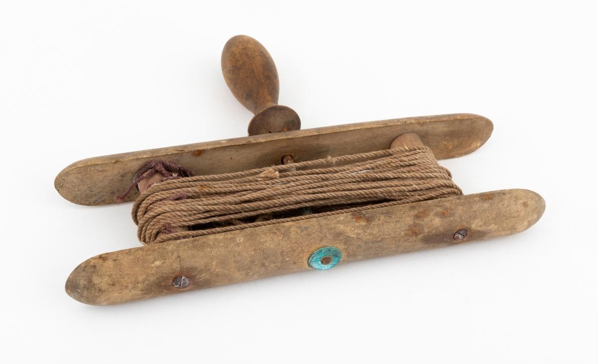Lita snørevinne med snøre. Vinna er laget av tre. Den består av to langsgående parallelle trestykker (2 cm brede). 3,2 cm fra enden av disse går det et rundt tverrtre mellom dem på hver side. Disse er festet med skruer av metall. På midten har vinna et dreid håndtak med en aksling i metall som går gjennom de langsgående trestykkene. Det er irr og rust på metallet. Snørevinna ser ut til å være fabrikklaget. Det er vinnet opp et fiskesnøre i bomull mellom tverrtrærne på vinna.
