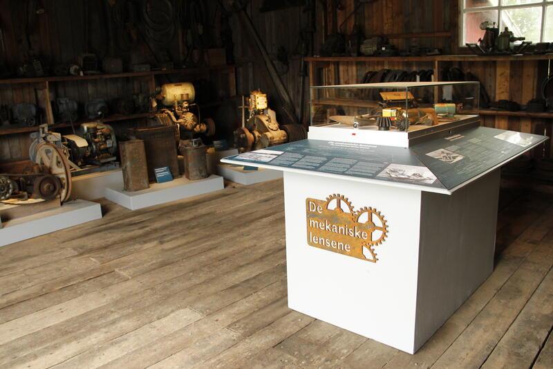 Foto fra utstilling med gamle motorer og mekaniske innretninger. I høyre kant sees et monter med mindre gjenstander og tekstplansjer. (Foto/Photo)
