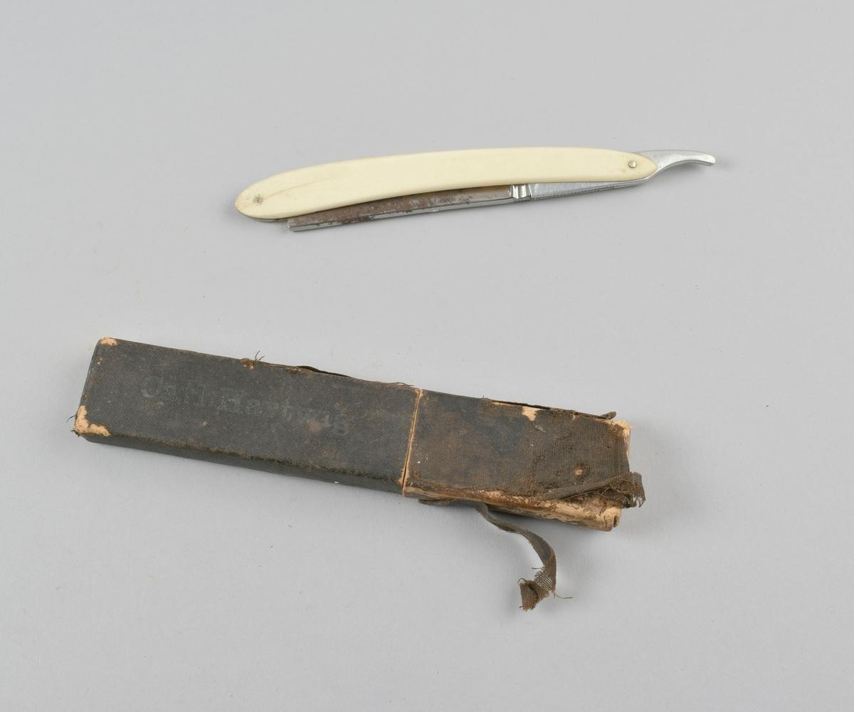 Sammenleggbar barberkniv med skaft i benmateriale, i futteral av papp kledd med tekstil.