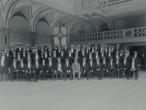 """""""Manskören Hallands sångarförbund. Kören bestod av personer från Halmstads sångarförbund, Varbergs musiksällskaps manskvartett, Falkenbergs manskör och Laholms manskvartett. De har just uppfört de sånger som de skulle sjunga vid Olympiska spelen i Stockholm under juli månad. Körsammansättningen gick under namnet Olympiakören."""""""