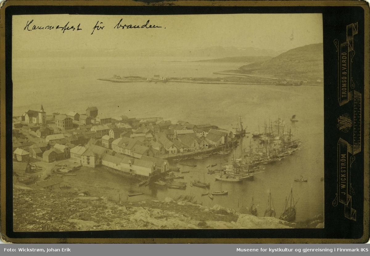 Bildet av Hammerfest før bybrannen 1890. Den tidligere kirken viser dette. Til høyre ser man havna med båter, kaianlegg og pakkhus. I bakgrunn til høyre ser man Fuglenes.