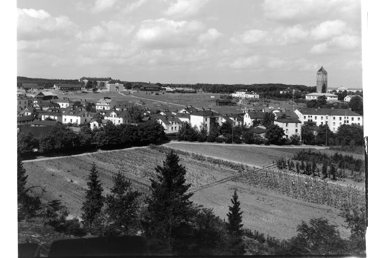 Vy från Belvederen mot T1 i väster, Linköping (serie 5/6). Stadsbebyggelse. Åker. Vattentornet i Linköping.
