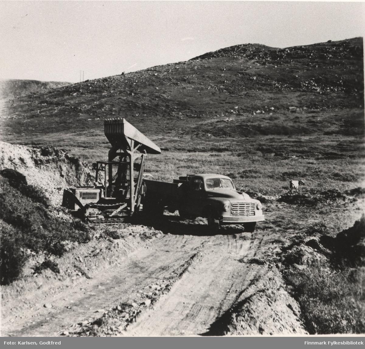 Her ser vi fyllmassekjøring i Sandfjord, ca. midt i mellom Mehamn og Gamvik. Dette er første lastemaskin de hadde på Nordkyn. Eieren er Hilmar Nilsen fra Honningsvåg. Studebaker lastebil modell 2R årsmodell 1949-53. Anlegg: Mehamn-Gamvik.