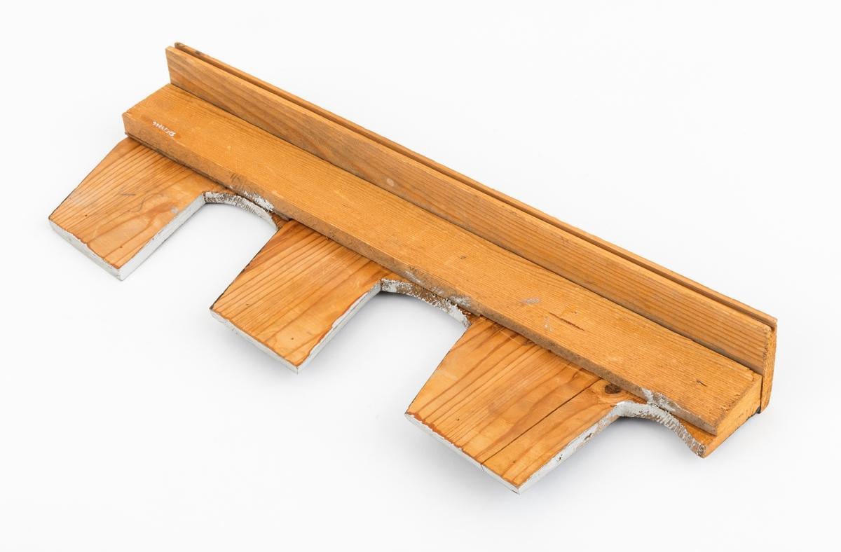 """Modell i tre av sagkjede, motorsagkjede av rivtannstypen. Tre sagtenner utført i treverk er spikret fast til en sokkel. På innsiden er det spikret fast en trelekt for oppstiving av """"tannkonstruksjonen"""". De tre tennene har påført svart maling på framsiden. De delene av tennene som skal files, er påført hvit maling. Modellen er brukt i undervisningen ved skogskolen på Sønsterud i Åsnes kommune for å gi elevene innblikk sagkjeders konstruksjon og vedlikhold."""