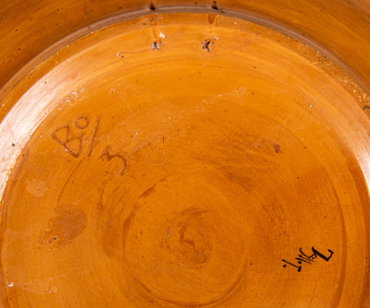 Väggfat, dalamotiv med dalkulla, kurbitsblommor, fågel och textsträng runt kanten: Hon kommer utför ängarna wid Sjugare by, hon är en liten kulla med mandelblommans hy. Sjugare by ligger i Leksands socken och kommun. Dräkten som den avmålade kvinnan bär påminner om Leksandsdräkten, men är ingen exakt återgivning. På undersidan finns en handmålad signatur som högst troligt är dekoratörens signatur. Den har tyvärr inte kunnat tydas.