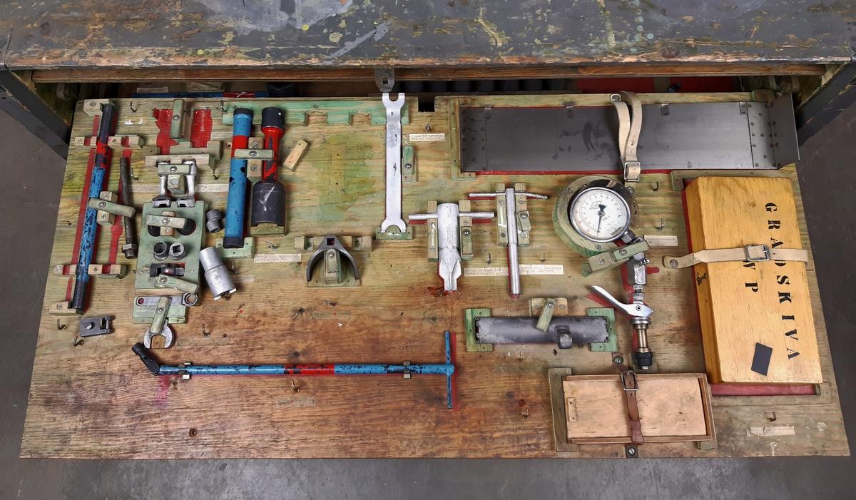 """Verktygssats 201 SK16, bestående av en grå förvaringslåda av trä med fyra utdragbara fack. Utsidan märkt med röda bokstäver: """"SE2-16"""", """"0309"""". Innehåller olika verktyg såsom gradskiva, nitverktyg, haknycklar, hylsnycklar, tappnycklar, samt smörjsprutor. Medföljer en satslista, samt ett avklippt hänglås."""