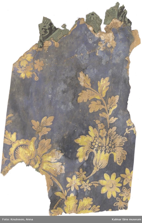 KLM 44016:1 Tapet i papper. Tapeten har flera lager. Lager 1 har svart bakgrund med pappersfärgade och gula blommor och blad. Lager 2 har pappersfärgad botten och blommönster i vitt. Lager 3 har gröngrå botten med svarta medaljonger med blommor i. Datering: lager 1: 1860-1870-tal, lager 2: 1860-1870-tal, lager 3 1880-1890-tal.