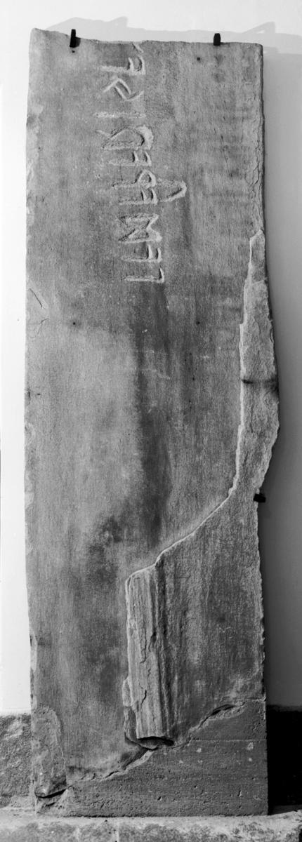 Avlang stein med runeinskripsjon, brukt som sidehelle i gravkammer.