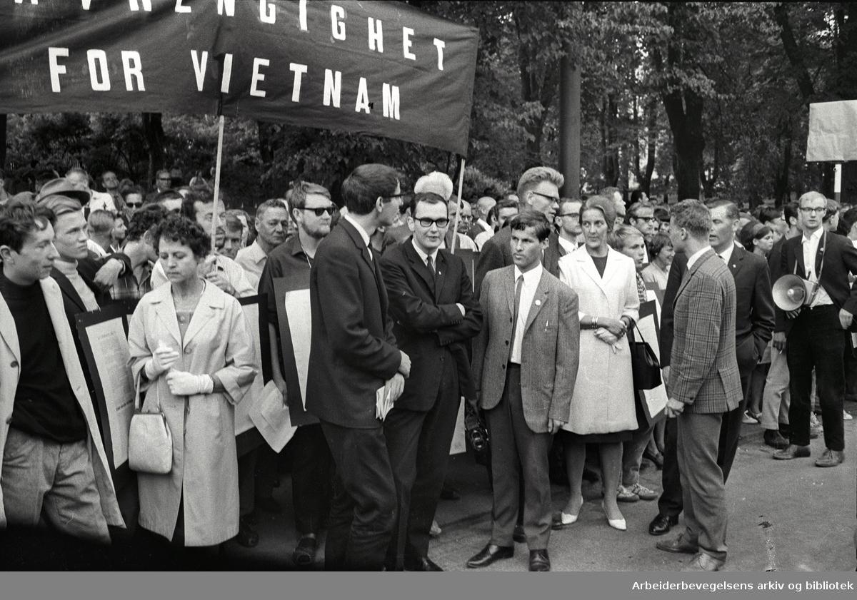 Demonstrasjon mot USA's krigføring i Vietnam utenfor Den amerikanske ambassade på Drammensveien (Nå Henrik Ibsens gate) i Oslo. I forgrunnen ses bl.a.: Ola Metliaas, Arvid Jacobsen, Ingrid Eide, Einar Førde, Thorbjørn Berntsen og Sigurd Allern (med megafon). 4. juli 1966.