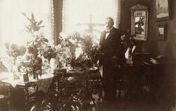 Landsfiskal Gustaf Herrlin, Åseda, poserar i sitt vardagsrum