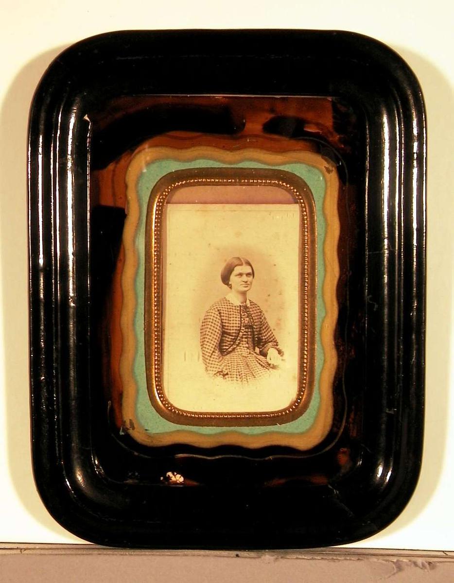 Portrett; ung kvinne sittende på stol med venstre arm hvilende på armlenet. Hun er kledd i en rutete kjole med tilhørende jakke med rysjekant og en liten hvit blondekrave rundt halsen. Frisyren har midtskill og det lange håret er samlet og satt opp bak.