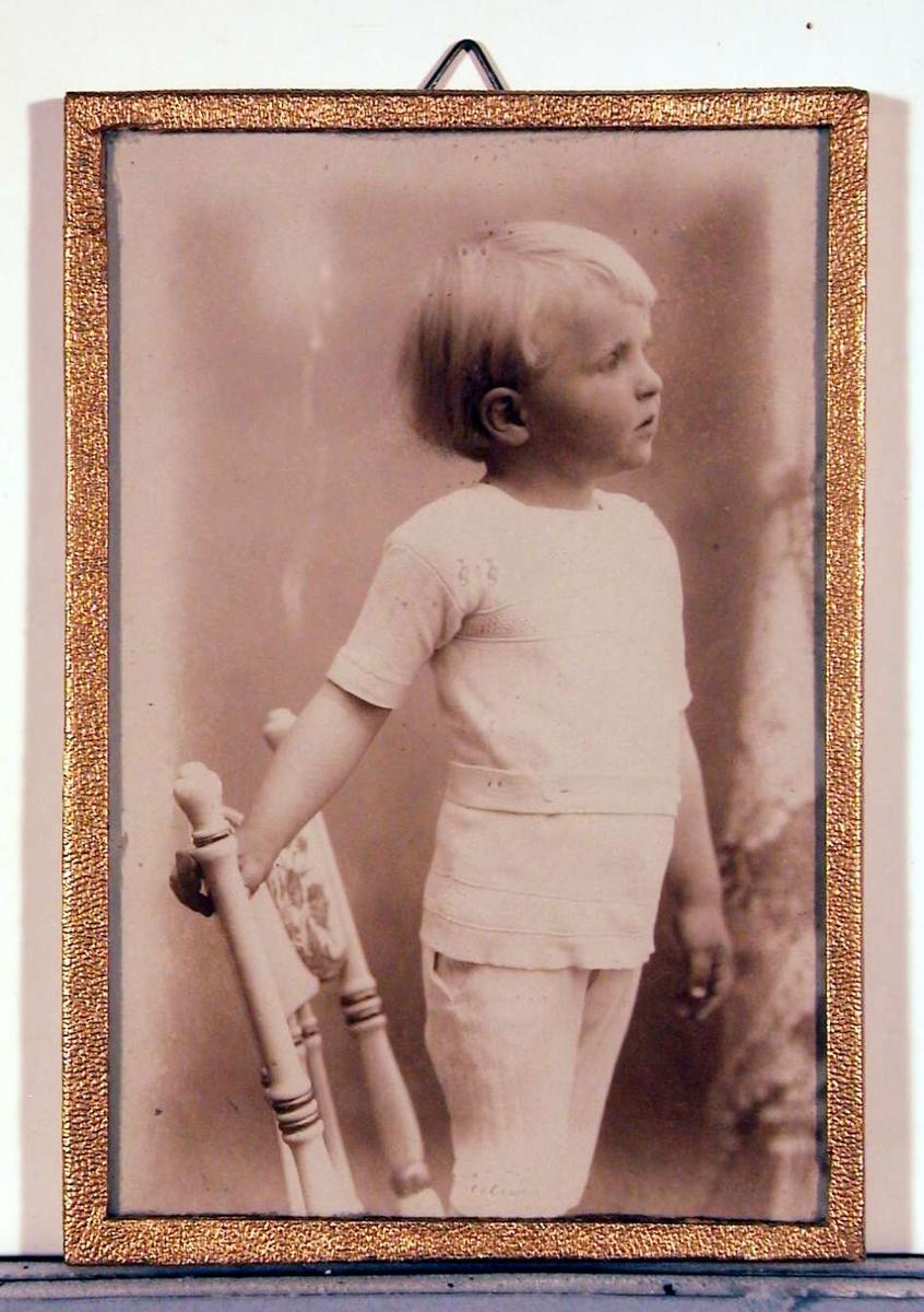 Barnebilde; fotografi av gutt stående i profil på stol.