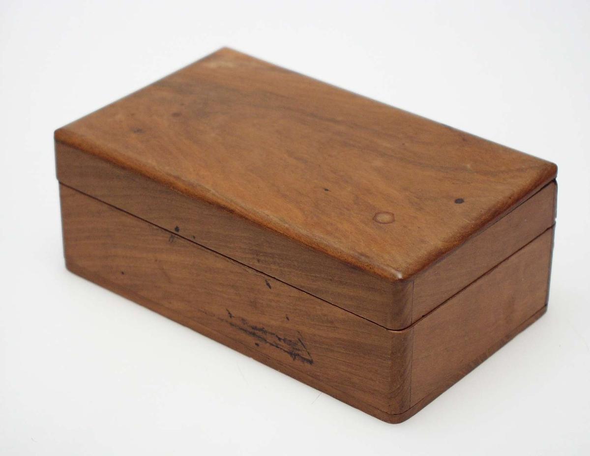 Treskrin med henglset lokk og avrundede kanter. Materialet ligner oliventre.