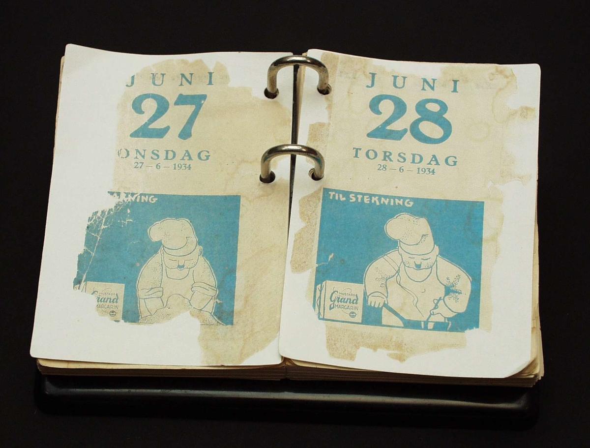 Bordkalender med svart metallholder. Kalenderen har blått reklametrykk.