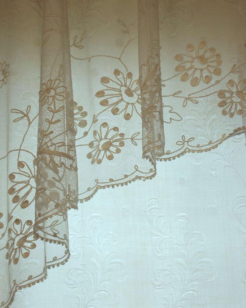 En bredde 150 cm er delt i to. 13-14 cm bord i ene siden med rettstrekte stilker, blad og blomster. Resten  av gardinen enkle, skråstilte tambursømlinjer som danner ruter 40 cm høye, 20 cm brede, vekselsvis to og tre hele ruter i høyden. Kantavslutning med åpen løkkebord og ytterst tett løkkebord i ene siden inn mot vinduet, i andre siden påsydd smal maskinsydd blonde av langsgående ovaler. Pga deling må annenhver gardin henge med vrangen ut.