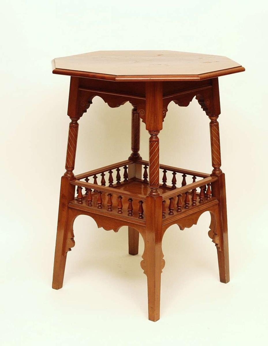 Bord i flammebjørk med åttekantet bordplate og hylle under. Det er er dekorert med innfeldte ornameter i metall.