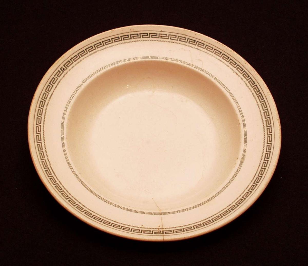 Dyp tallerken i steintøy. Den er hvit med grønn meanderbord.