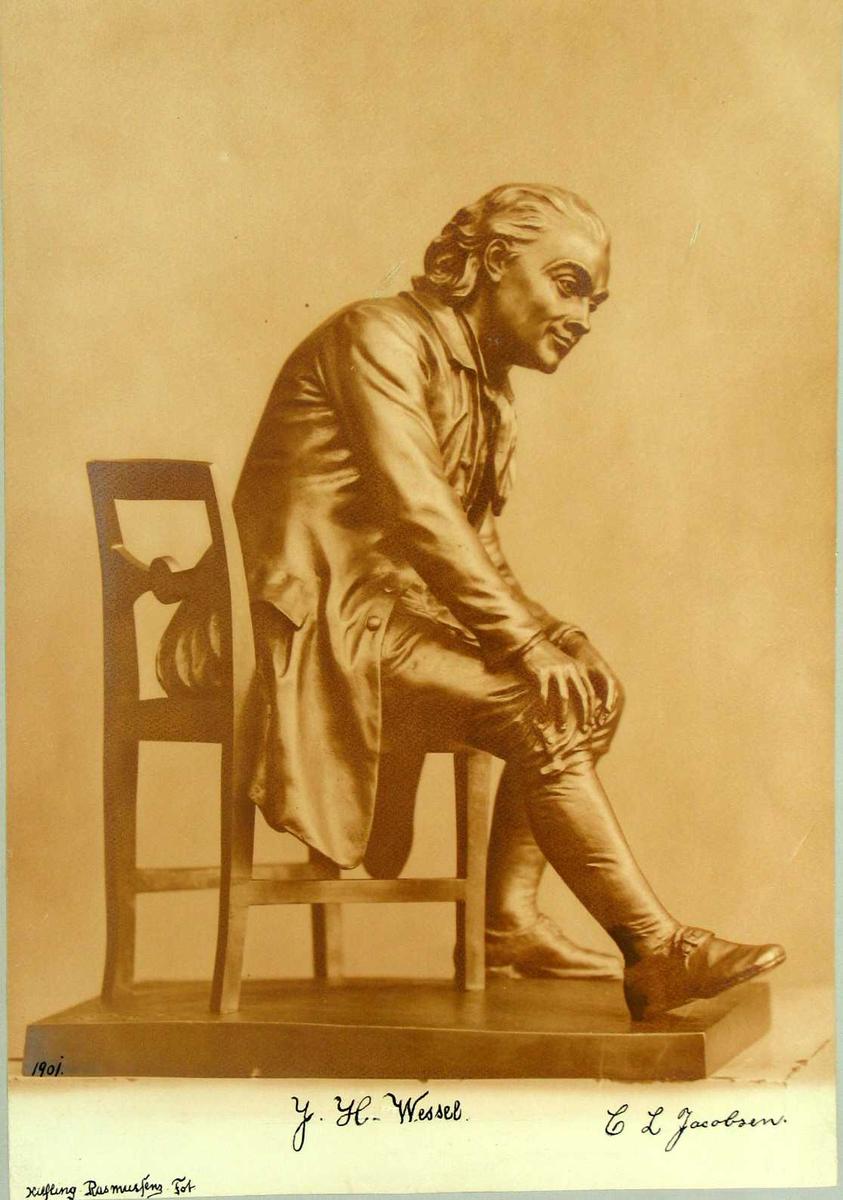Fotografi av en skulptur limt på grå kartong.