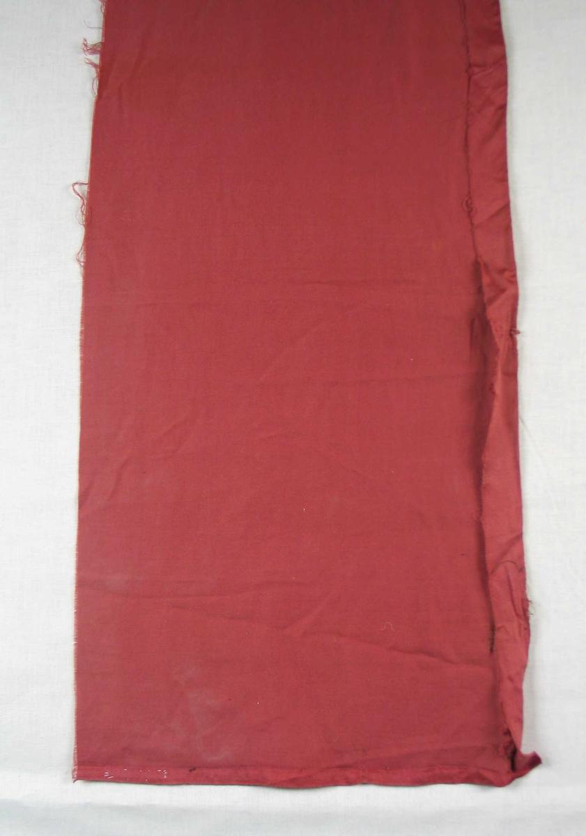 Rest av fôr brukt i portiere. Materialet er rød bomullssateng.
