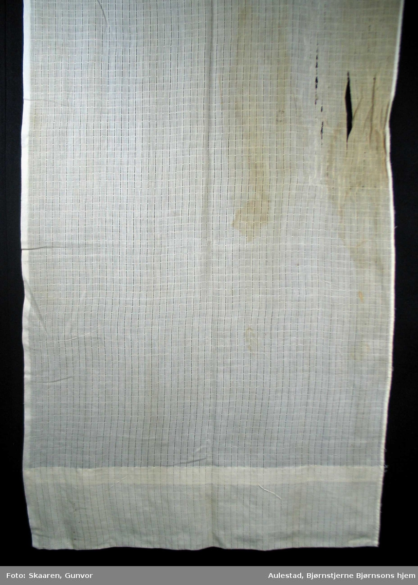 Hvit undergardin i gjennombrutt bomullsstoff. Striper både på langs og tvers danner ruter, ca.1cm. 17 cm bred oppbrett nederst