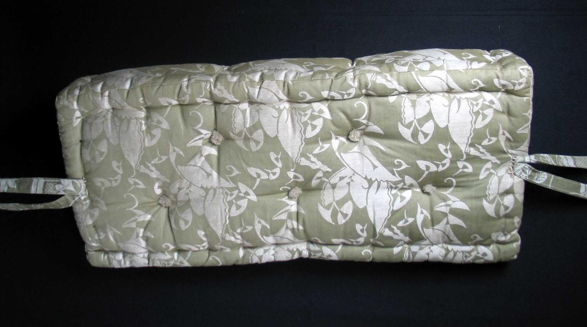 Grønn og grå mønstervevd skråpute i bomull. Den har påsydd to bånd i hver ende med metallring ytterst. Stikninger langs kanten og små dusker i ull.