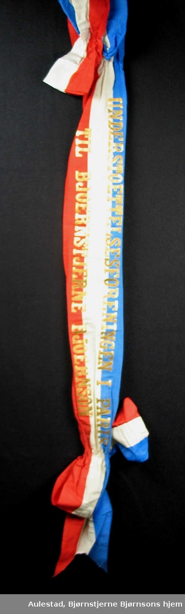 Begravelsessløyfe i rød, hvit og blå silke med skrift i gull.