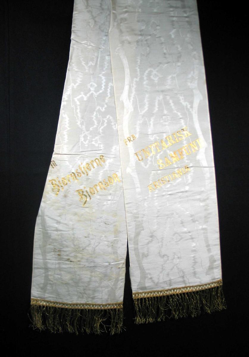 Begravelsessløyfe i hvit silke med tekst og frynser i gull.