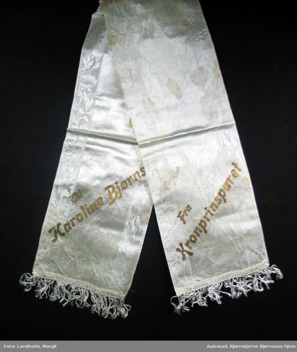 Begravelsessløyfe i hvit mønstret silke med tekst i gull.