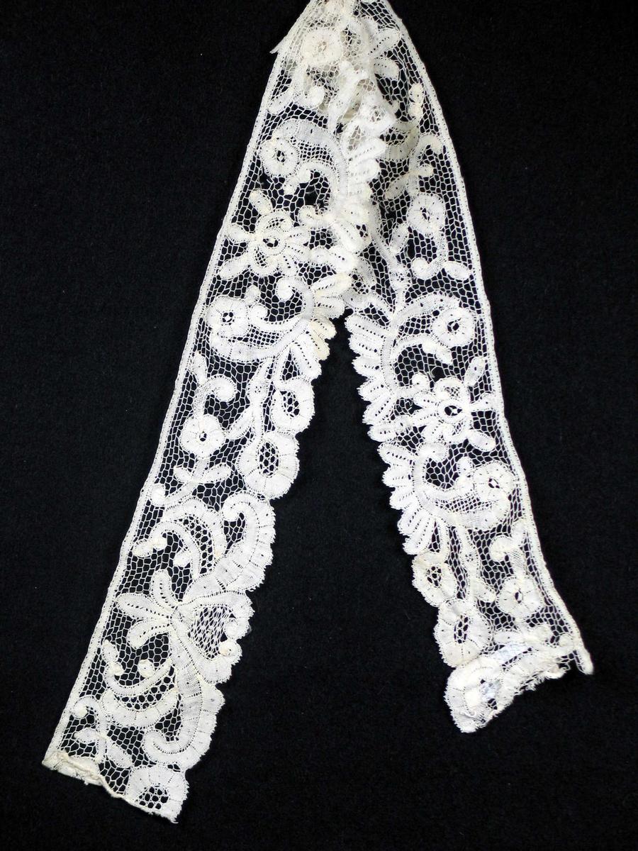 Hvit kniplingsblonde med åpen nettverksbunn (tyll?). Mønster i lerretsbinding, stilisert blomster- og bladmotiv. En mønsterrapport: 31 cm.