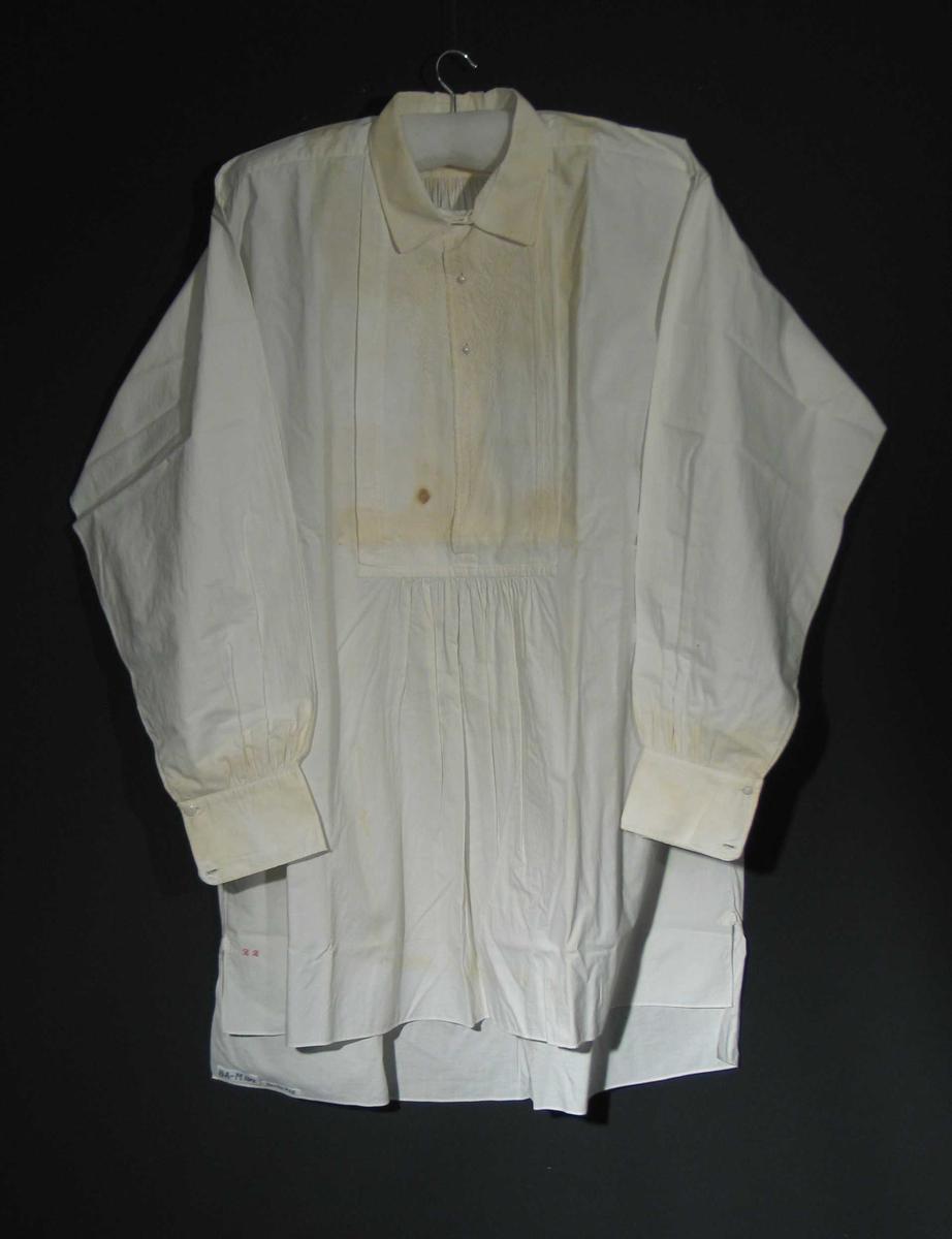 Hvit skjorte med broderi med motiv: blomster og bladverk. Monogram. Skjortebolen av hel stoffbredde, sydd sammen jare mot jare med tette kastesteng. Stoffbredde 83 cm. 8 cm splitt i sidesøm, forsterket innsplittsnitt. Forstykket er 6 cm kortere enn bakstykket. Dobbelt skulderstykke, trådrett, søm i nakken, rett krage med spisse hjørner og underkrage. Ryggstykket rynket inn i skulderstykket. Innfeldt forstykke med broderi og fôret med linlerret, 39x21 cm, med lukning med to knapphull på hver side. Nedre del av forstykket rynket opp i forstykket og forsterket med en 21x1 cm vertikal stolpe. Svakt skrådd ermringning på forstykket. Ermet er sydd sammen med to til tre mm indresøm og sydd til bolen med 8 mm indresøm. Ermet er rynket til håndlinning 26x8 cm. Atterstingstikning 5 mm fra kanten og et knapphull med knapp nær 10 cm lang splitt og to knapphull for skjorteknapp ved linningens avrundede hjørner. Monogram med rosa korssting måler 18x6mm og er plassert ved splittsmutten på høyre forstykke. To knapphull ytterst på linning er sydd senere.