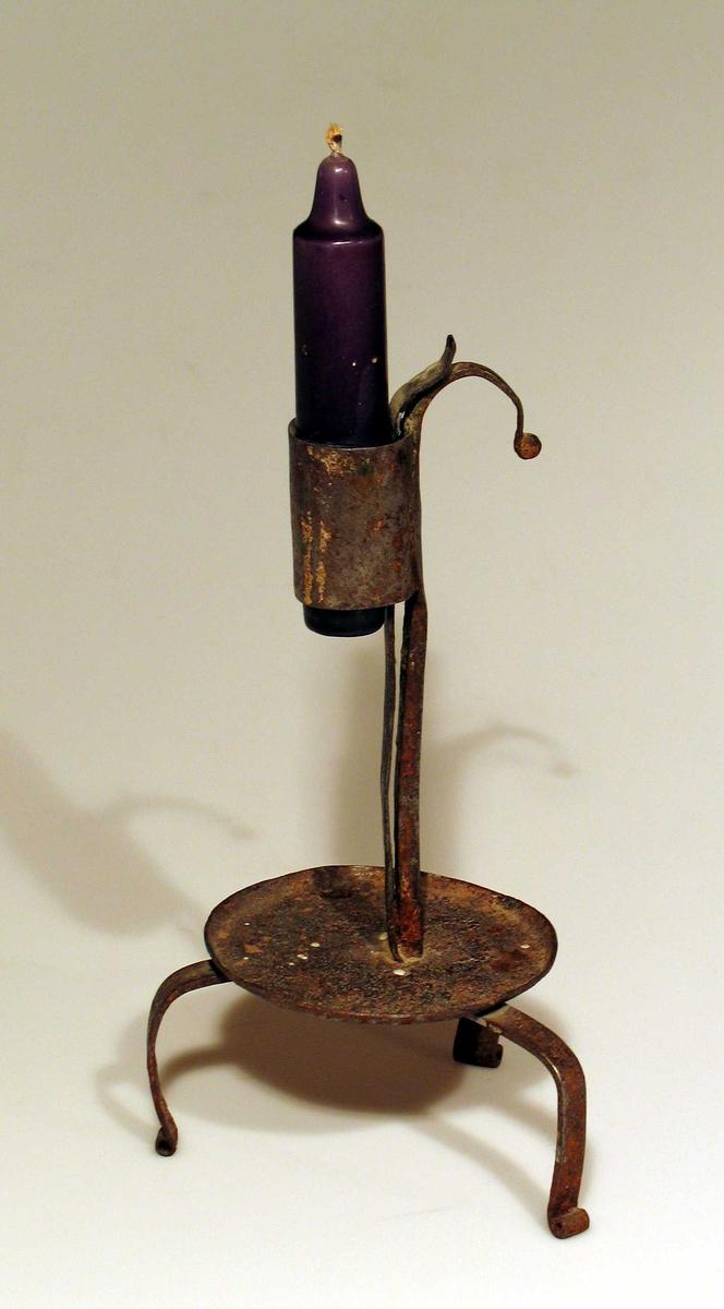 Lysestake i jern med tre bøyde ben og dryppskål. Fjærbelastet lysholder. Rund hank.