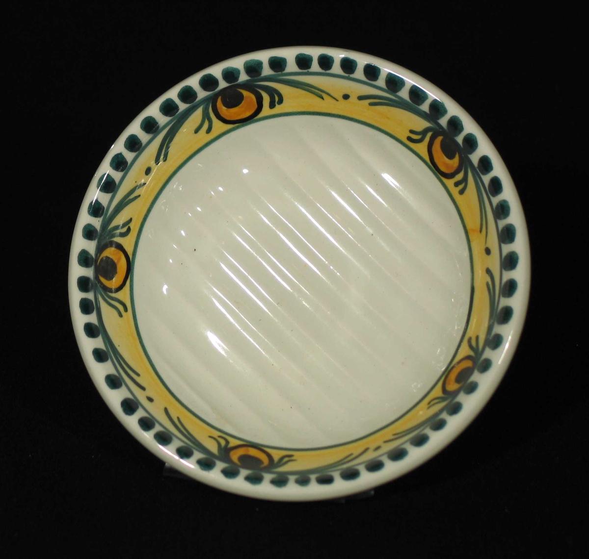 Rund hvit såpeskål i steintøy med riller i bunnen. Øverst en gul og hvit rand med blomsterdekor i grønt og svart.