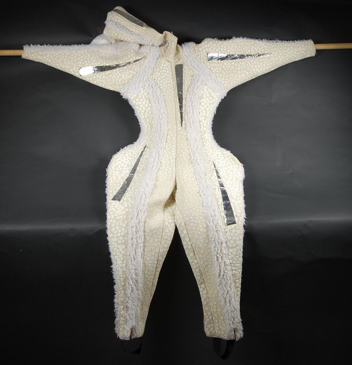 Hvit hel vettedrakt. Den er heldekkende for kropp og hode. Hetten har dusk. Det er sølvfargert dekor på dressen.