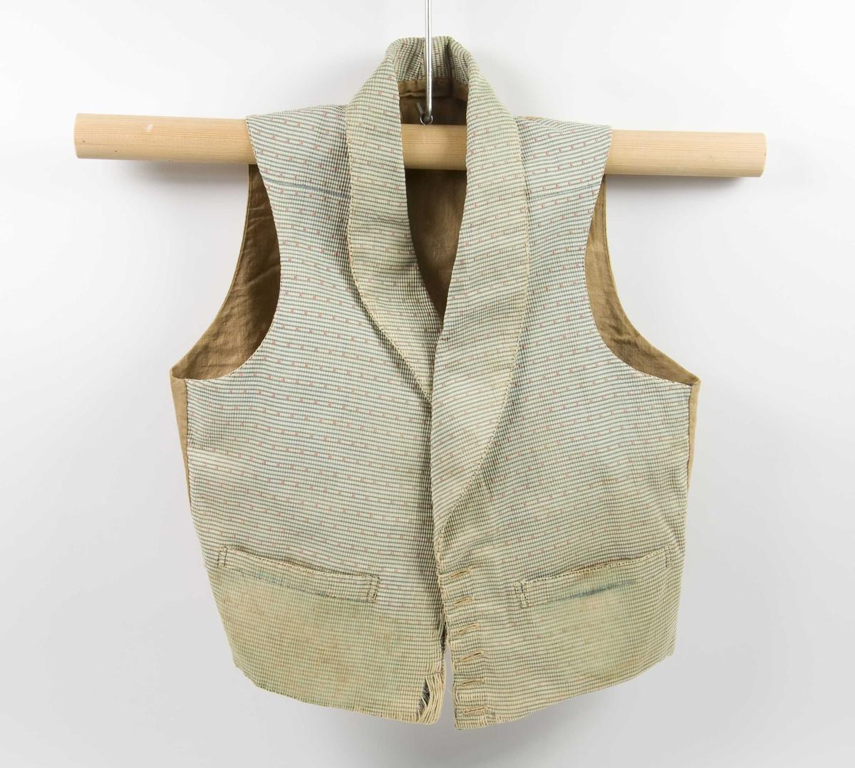 Håndsydd mannsvest av silke med ryggstykke og fôr av bomull. Vesten har nedbrettet sjalskrage og to sidelommer. rester av snøring i ryggen. Enkelspent med syv knapphull, mangler knapper. Forstykkene danner en spiss midt foran.