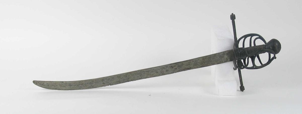 Soppformet knapp med strekdekor. Asymmetrisk kurvfeste med tre sidebøyler med riflede fortykkelser på midten mellom hånbøylen og kurvens ytterkant. Innsiden har to sidebøyler. Kurvens basis består av rektangulær parérplate med klingebrekker. Tommelbøyle på innsiden. Rette parérstenger med riflede fortykkelser på endene. Tregrep med nyere jerntrådvikling. Enegget krum flat klinge. Har rester av tre smedmerker på venstre side.