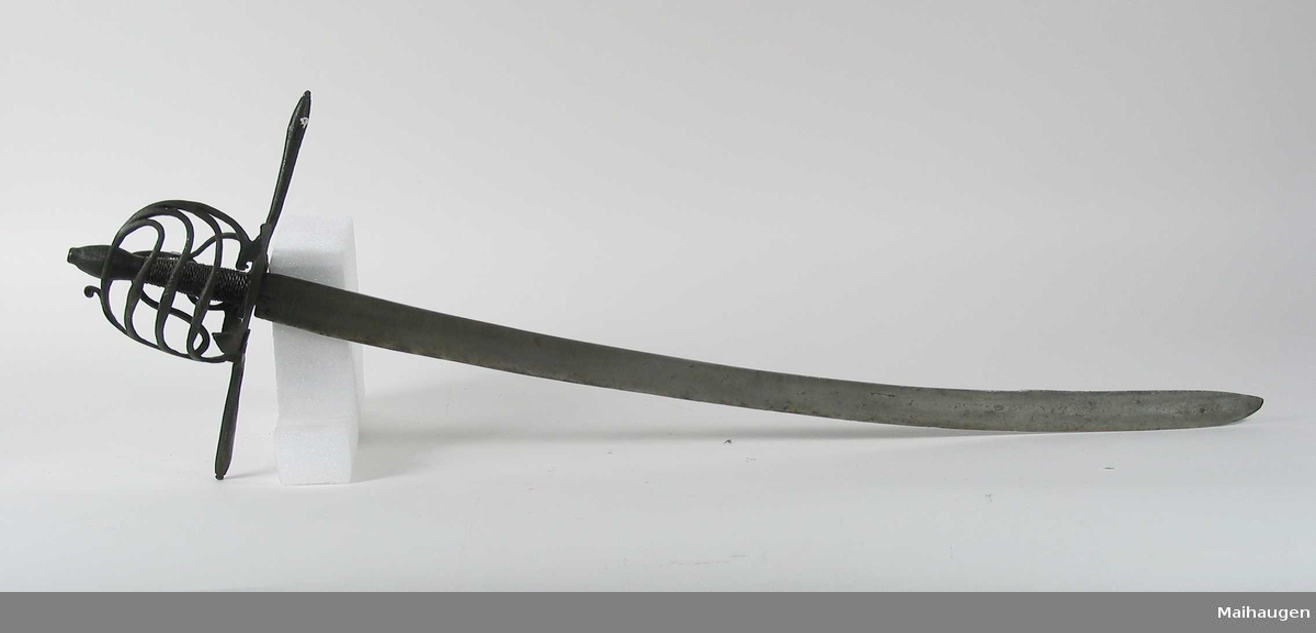 Rund knapp som er uorginal til våpenet. Asymmetrisk kurvfeste med tre sidebøyler med riflede fortykkelser på midten. Mellom håndbøylen og kurvens ytterkant. Innsiden har 2 sidebøyler og mangler tommelbøyle. Kurvens basis er en nyreformet parérplate med skade på utsiden.   Rette parérstenger ( den fremre er nyere og klinket på ) med riflet dekor på endene. Tregrep med jerntrådvikling. Enegget krum klinge. Bred hulslipning på ryggsiden.