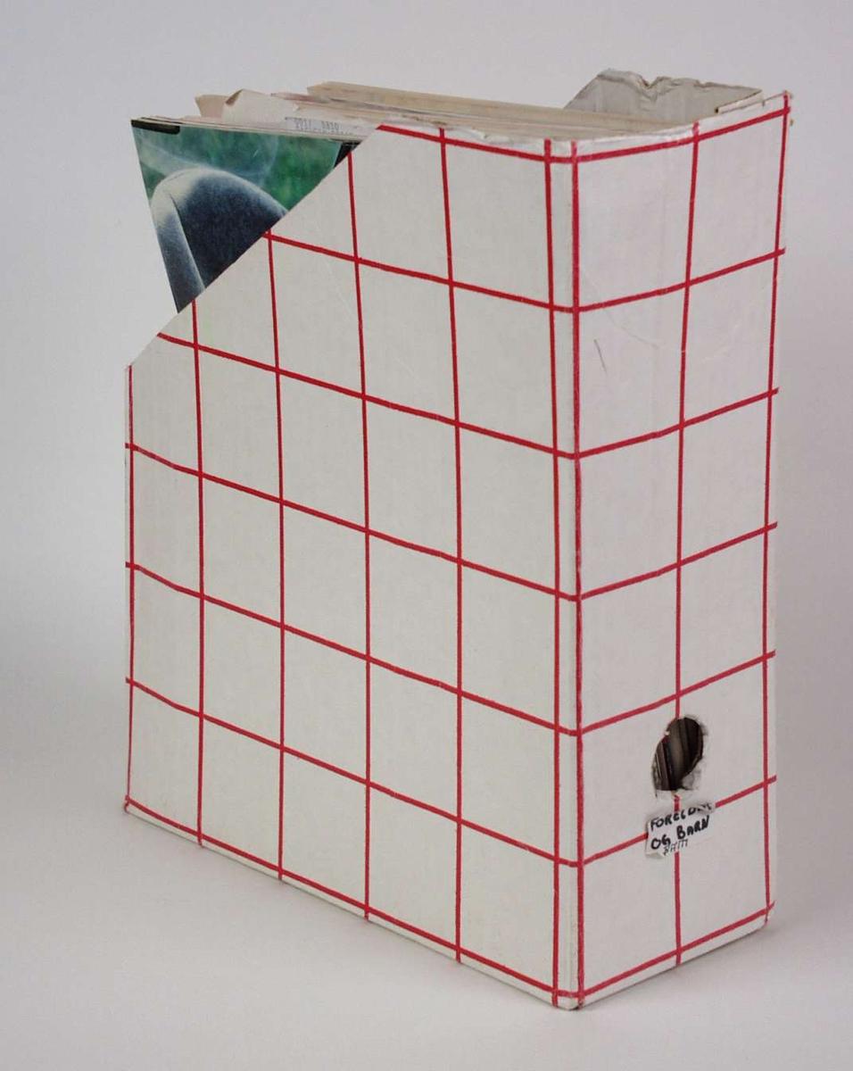 Hvit tidskriftsamler i kartong med rødt rutemønster.