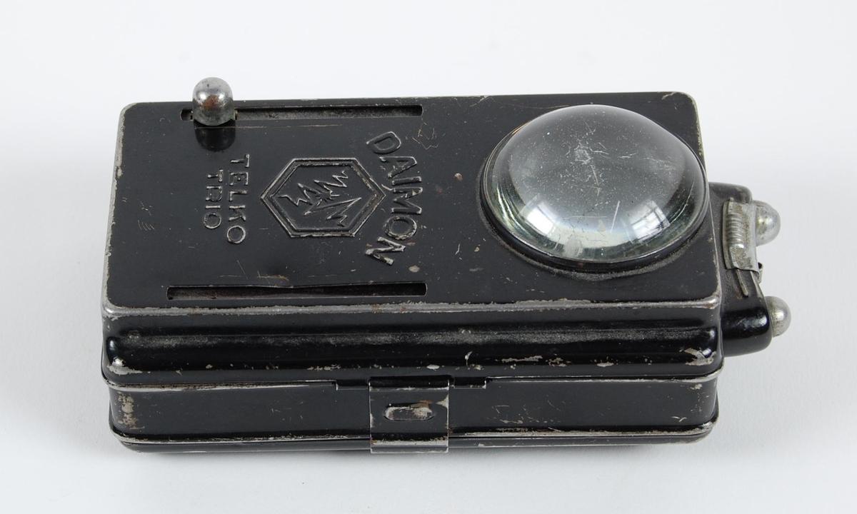 Sortlakkert metallykt med lærstropp for å feste i belte eller knapp. To reguleringsknapper på fremsiden for grønt og rødt lys. To knapper på toppen for kontinuerlig lys. Stort forstørrelsesglass i fremkanten.