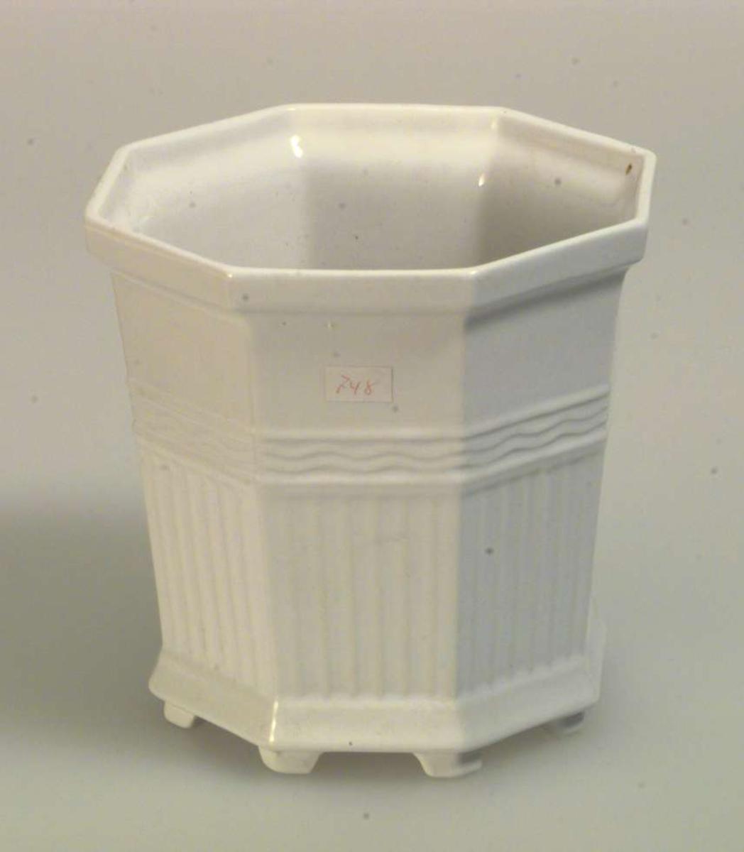 Blomsterpotteskjuler i keramikk. Den er åttekantet og står på åtte føtter. Den er hvit og har rillemønster.