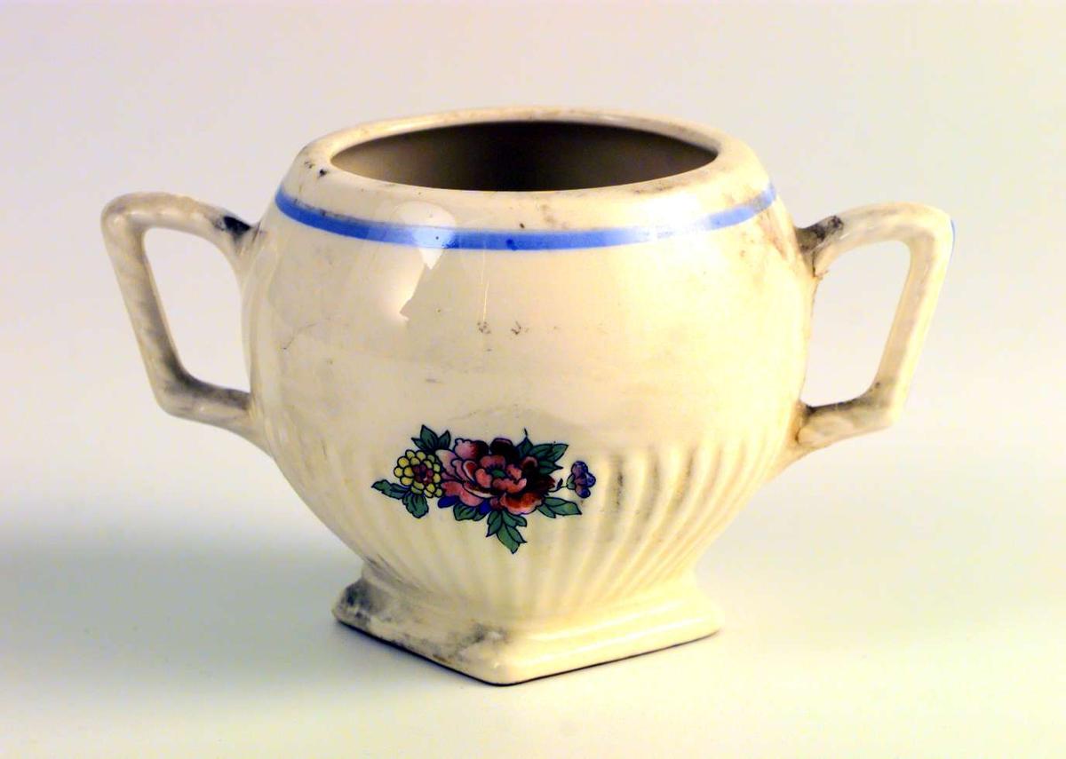 Sukkerkopp i gul keramikk. Den har rundt tverrsnitt og firkantet fot. Den har to hanker. Den har blomsterdekor. Sukkerkoppen mangler lokk.
